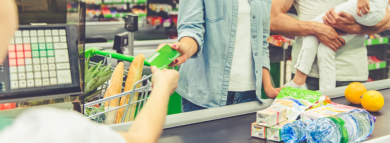 Parents with young child in supermarket checkout line