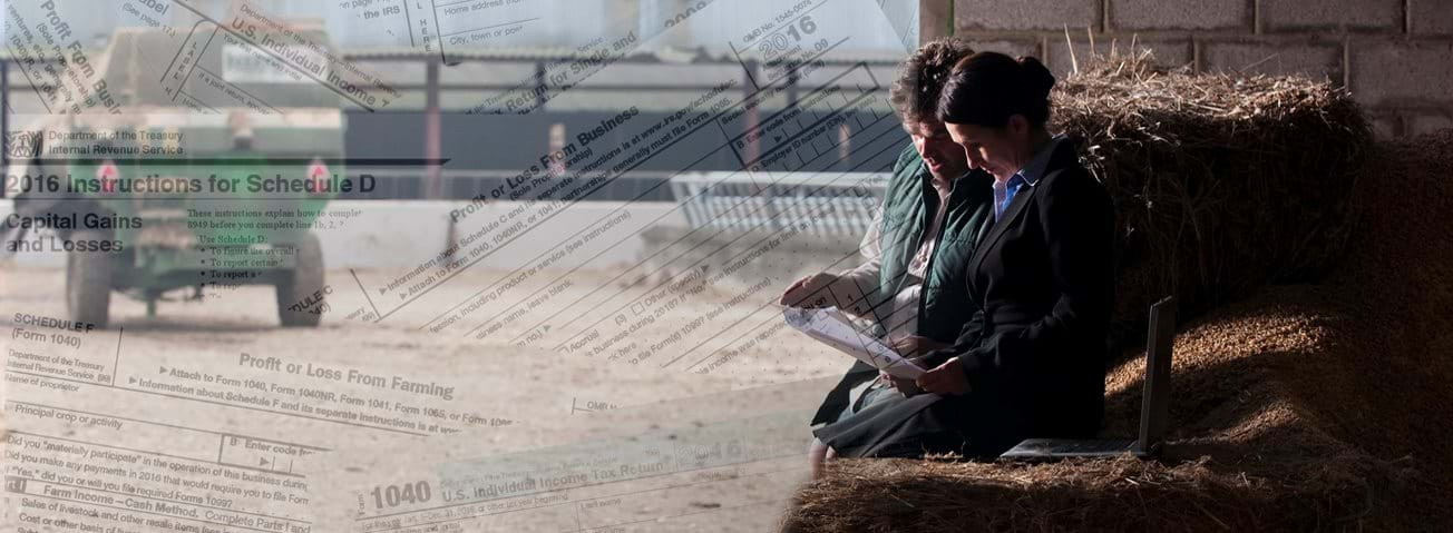 Composit image of tax forms superimposed over a woman and man reviewing documents with farm equipment in background