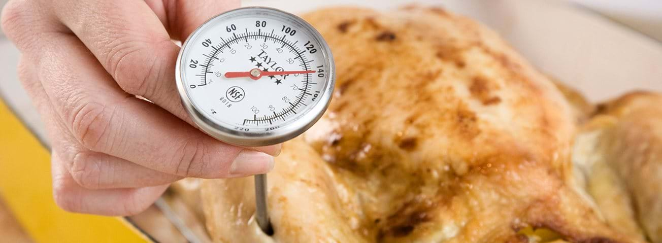 Closeup of a meat thermometer in baked poultry.