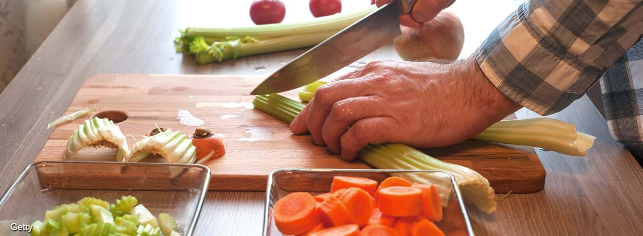 Man chopping vegetables for a meal.