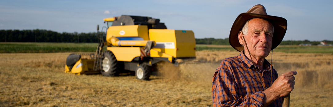 Photo of a farmer in his field, with combine in the background