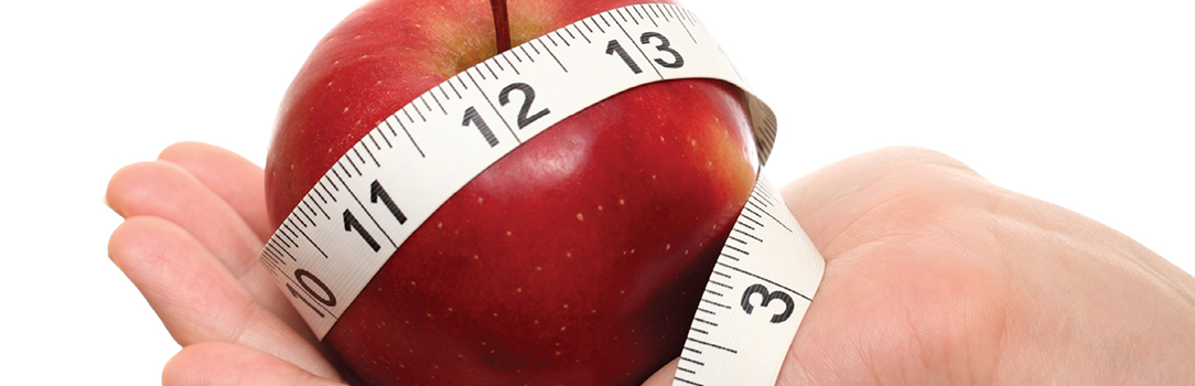 hand holding an apple encircled by a tape measure