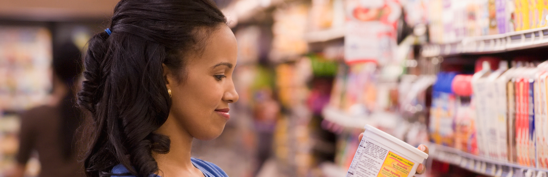 Woman inspecting item in grocery store aisle