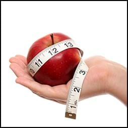 hand holding apple with measuring tape around it
