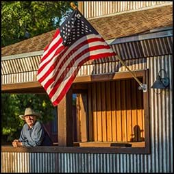 man on porch with american flag
