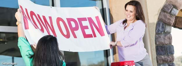 "Ladies hanging ""Now Open"" banner over the door of their new business"