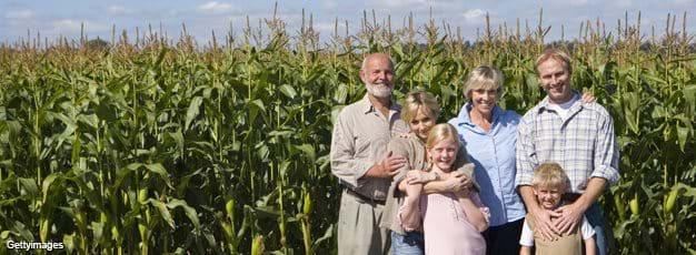 Farm family of three generations by corn field
