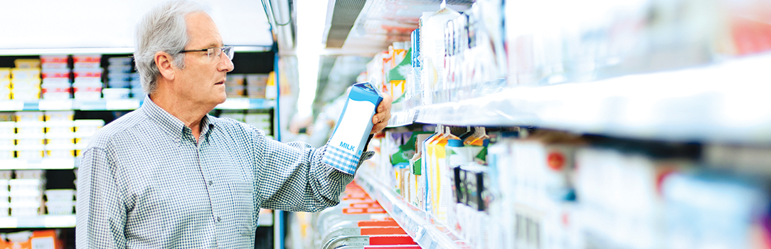 Man in grocery store reading milk carton label