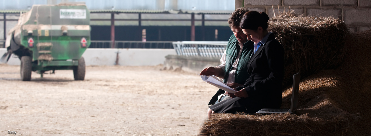 Farmer and wife looking at paperwork with farm scene in the background