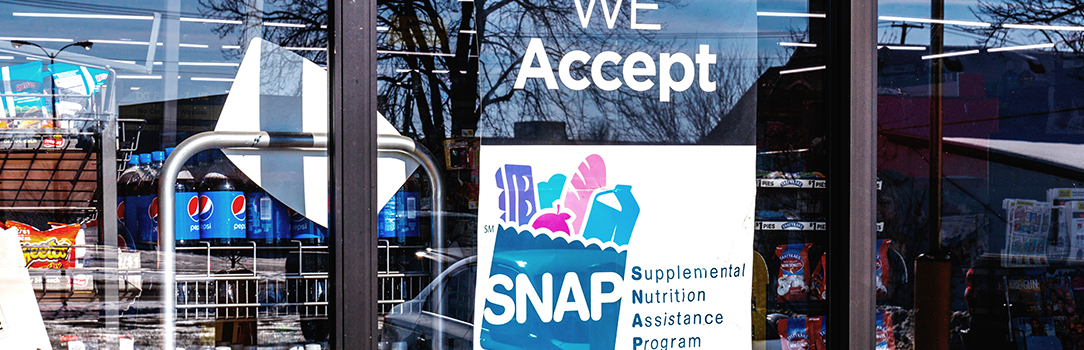 """We Accept SNAP"" sign in grocery store window"